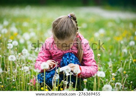 Little girl checking and reviewing photos she made with digital camera, enjoying her time on a dandelion meadow. Active lifestyle, curiosity, pursuing a hobby, technology and kids concept.