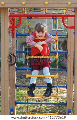 Little girl cheerfully smiles on ladder playground in sunny autumn day - stock photo