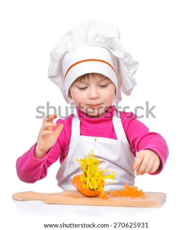 Little girl chef cuts fresh vegetables on wooden board isolated on white background. - stock photo