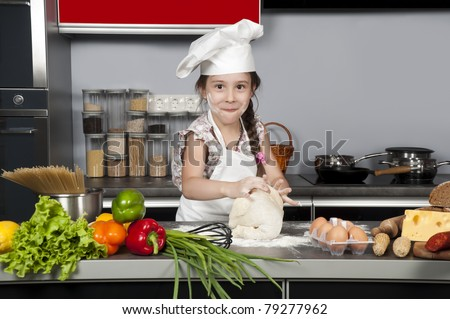 little girl chef knead the dough on the kitchen table with raw food
