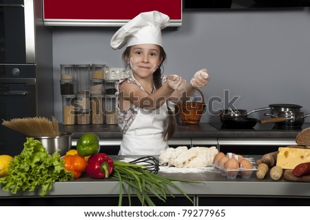 little girl chef knead the dough on the kitchen table with raw food - stock photo