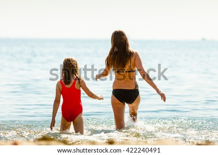 Little girl child and mother having fun in ocean. Kid and woman bathing in sea water. Summer vacation holiday relax. - stock photo