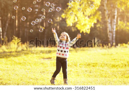 Little girl child enjoying playing with soap bubbles in autumn park - stock photo