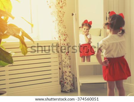 little girl child fashionista looking in the mirror at home in a red skirt, shoes of mother - stock photo