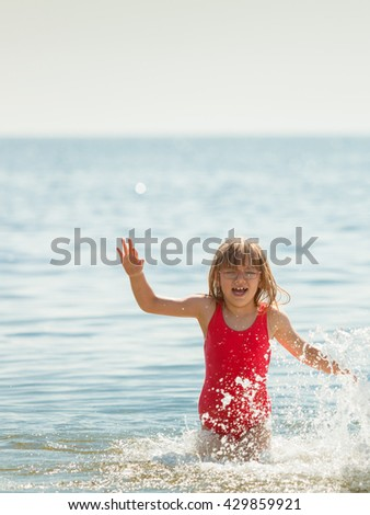 Little girl child having fun in ocean. Kid and woman bathing in sea water. Summer vacation holiday relax. - stock photo
