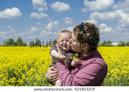 Little Girl Child  in father's arms. Man kissing daughter on her cheek. Family and love. Yellow rapeseed flowers on field with blue sky and clouds