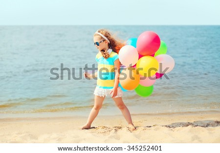 Little girl child on summer beach playing with colorful balloons near sea - stock photo