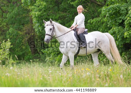Little girl child walks on a white horse on the field - stock photo