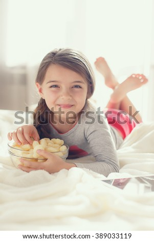 Little girl child with remote control watching tv set lying on bed in room. 6 years old child watching tv laying down on a white carpet at home alone. cute little girl - stock photo