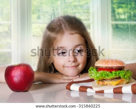 Little girl choose between healthy and harmful food.Kid hesitating between apple and hamburger.Child's nutrition. - stock photo