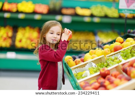 Little girl choosing a bio apple in a store - stock photo