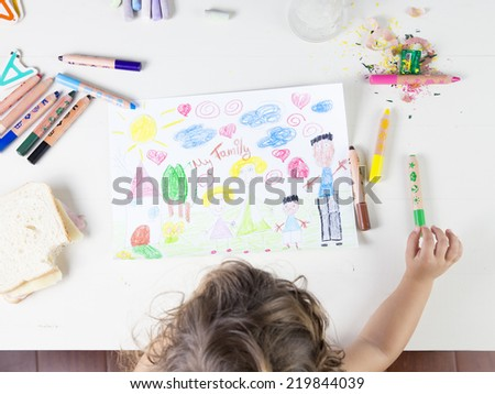 Little girl choosing a green pencil in a wood table. Multi-racial Family drawing on a white paper witch coloured pencils, a sharpener, chalks and a sandwich that has been bitten once - stock photo