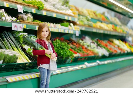 Little girl choosing a leek in a food store - stock photo