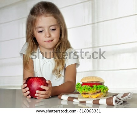 Little girl choosing between healthy and harmful food.Child with apple and hamburger. - stock photo