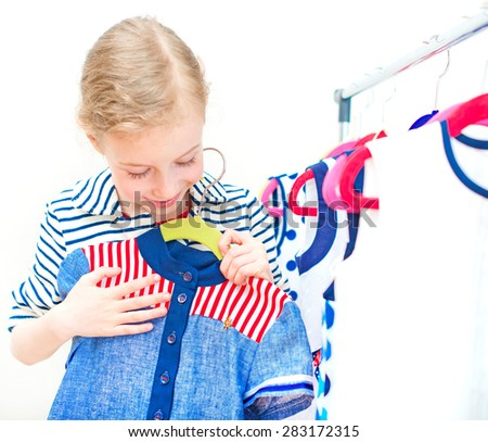 Little girl choosing dress in clothing store. - stock photo