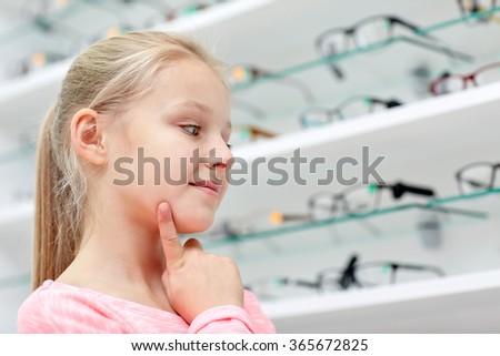 little girl choosing glasses at optics store - stock photo