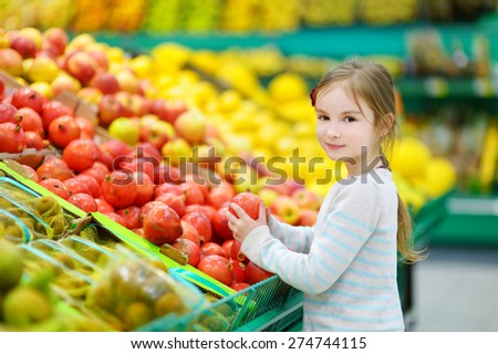 Little girl choosing pomegranates in a food store or a supermarket - stock photo