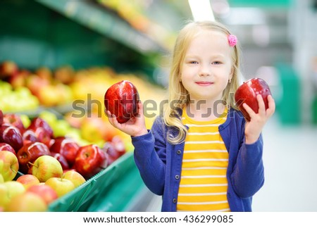Little girl choosing ripe apples in a food store or a supermarket - stock photo