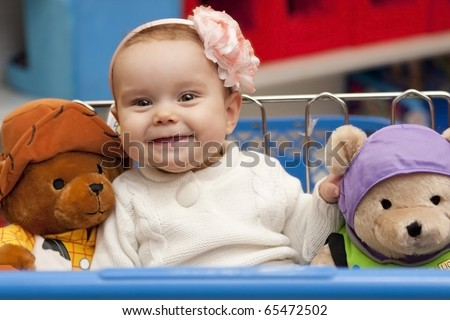 Little girl Christmas shopping for toys with stuffed animals besides her in cart. - stock photo