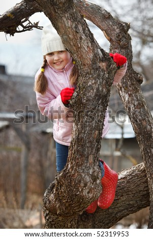 Little girl climbed on tree and sitting on tree branch, low angle view