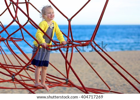 Little girl climbing in beach playground. Family with children enjoying vacation at the sea. Active kid having fun outdoors. - stock photo