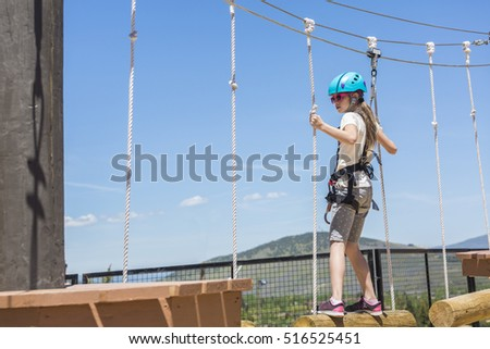 Little girl climbing on an outdoor ropes course