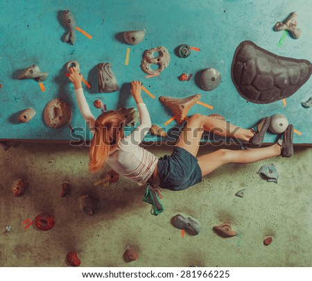 Little girl climbing on artificial boulders in gym - stock photo