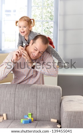 Little girl climbing on father's back, having fun, laughing.