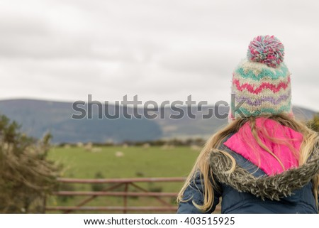 little girl climbing over a farm fence with sheep in background