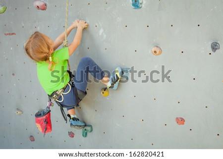 Little Girl Climbing Rock Wall - stock photo