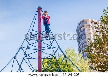 Little girl climbing up high on children playground. Child make a challenge to yourself.   - stock photo