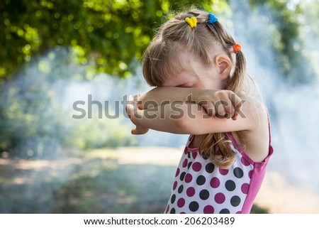 Little girl closed eyes her arms, natural background - stock photo