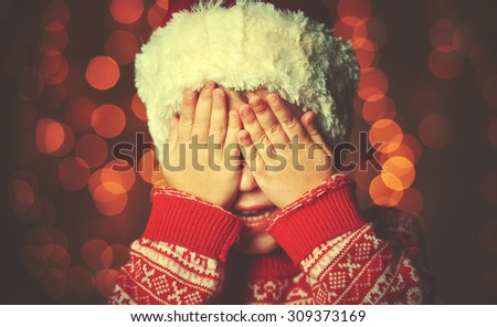 little girl closed eyes  her hands in anticipation of a Christmas miracle and a gift - stock photo