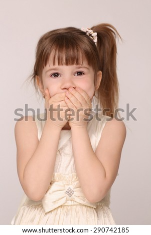 Little girl closed her mouth. Pretty girl in white dress isolated on white background.