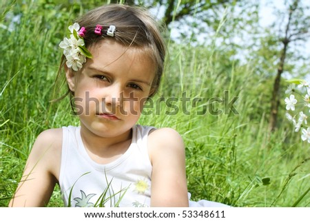 little girl closeup portrait with white flowers and grass