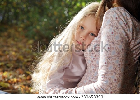 Little girl clung to her mother's chest listening heartbeat - stock photo