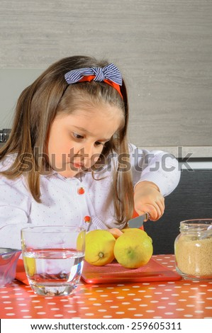 Little girl collaborating in the kitchen. - stock photo