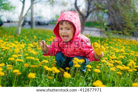 Little girl collects a bouquet of dandelions for her mother