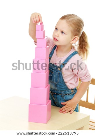Little girl collects the pink pyramid.Childhood education development in the Montessori school concept. Isolated on white background. - stock photo