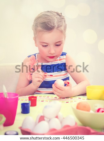 little girl coloring eggs at home - stock photo