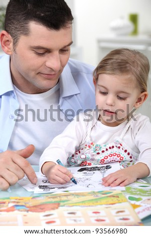 little girl colouring under dad's watchful eye - stock photo