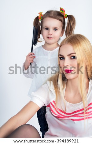 Little girl combing her hair beautiful mother