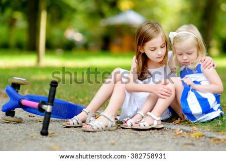 Little girl comforting her sister after she fell while riding her scooter at summer park - stock photo