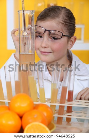 Little girl conducting experiment on oranges - stock photo