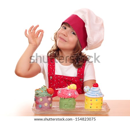 little girl cook with cupcakes and ok hand sign - stock photo