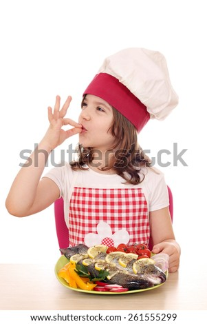 little girl cook with prepared trout on plate - stock photo