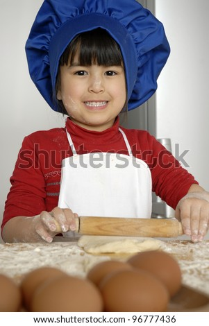 Little girl cooking a pizza in a kitchen.Little kid in a kitchen.Little girl cooking a pizza in a kitchen.Little kid in a kitchen. - stock photo