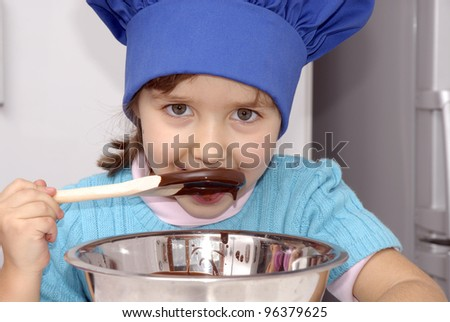 Little girl cooking chocolate in a kitchen.Little girl using a chef cap and cooking in a kitchen. - stock photo