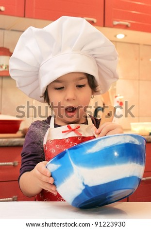 Little girl cooking in the kitchen - stock photo