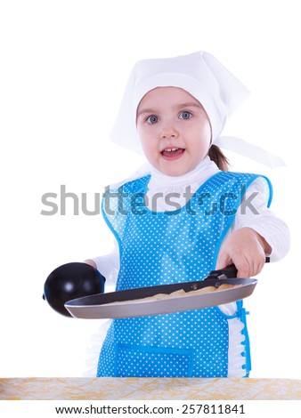 Little girl cooking pancakes. The child holding the pan and showing a pancake. Isolated on a white background. - stock photo